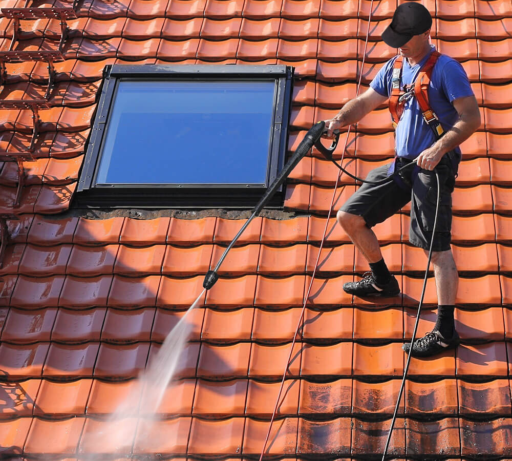 Man cleaning tiles with pressure washer